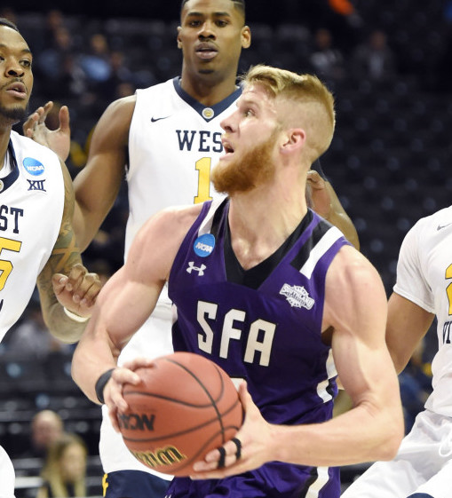 Mar 18, 2016; Brooklyn, NY, USA; Stephen F. Austin Lumberjacks forward Thomas Walkup (middle) drives to the basket against West Virginia Mountaineers players Elijah Macon (45) , Esa Ahmad (23) and Jonathan Holton (1) in the first half in the first round of the 2016 NCAA Tournament at Barclays Center. Mandatory Credit: Robert Deutsch-USA TODAY Sports